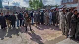 Indian paramilitary troopers stand guard as Kashmiris wait in queue to cast their votes during the second phase of Indian parliamentary-election on April 18, 2019, in Srinagar.